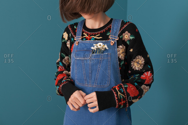 Woman wearing denim overalls with daisies in pocket