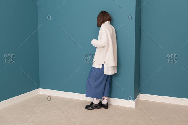 Young model wearing white sweater and denim dress leaning against blue wall