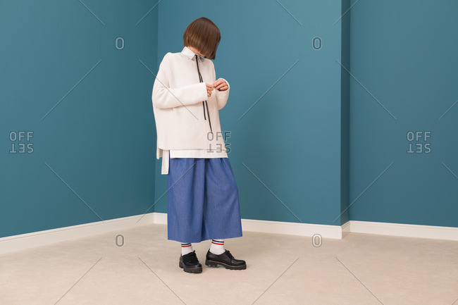 Young model wearing white sweater and denim dress in a blue room