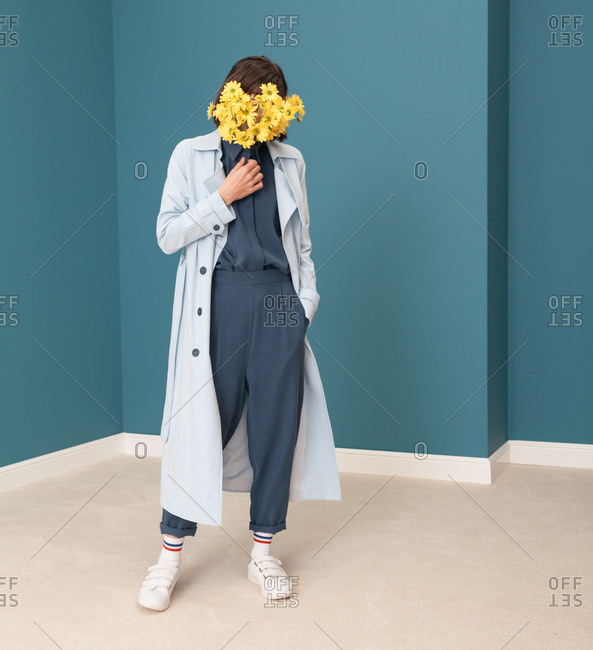 Young model wearing blue trench coat in a blue room with her face covered with flowers