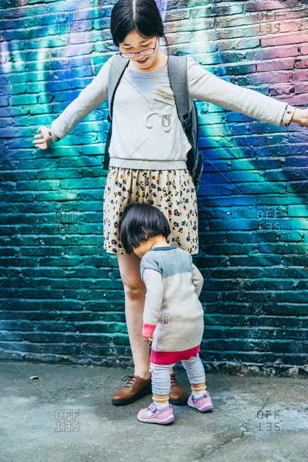 Mom and girl playing by urban wall