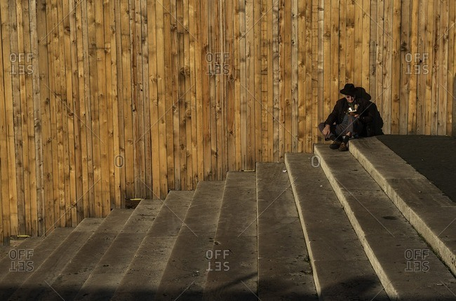 Rome, Italy - December 8, 2016: Man reading book on steps