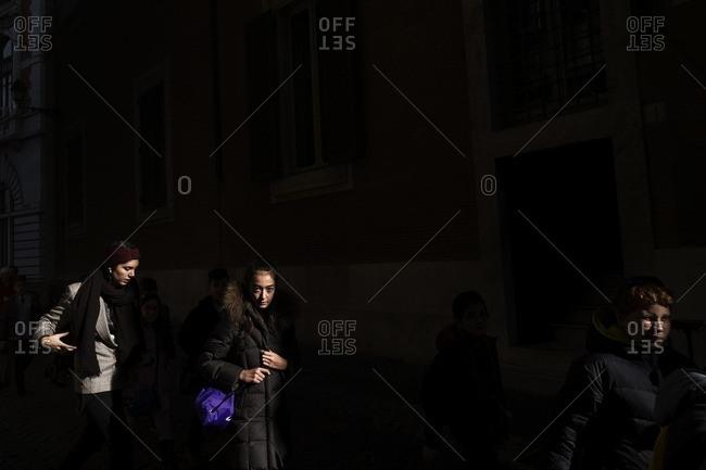 Rome, Italy - December 2, 2016: Women walking in shadowy street