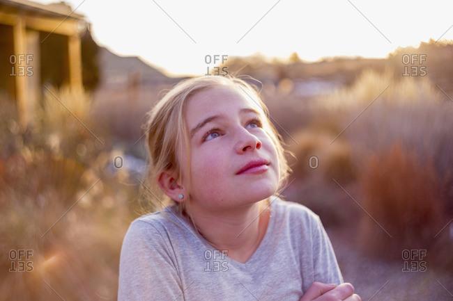 Girl gazing up in wonder outside