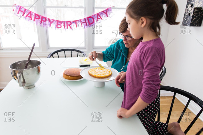 Girl and grandmother frosting birthday cake