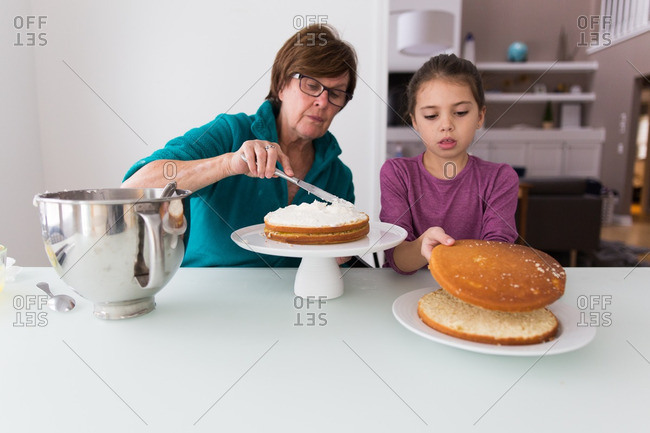 Girl and grandma frosting layered cake