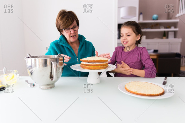 Girl and grandma assembling layered cake