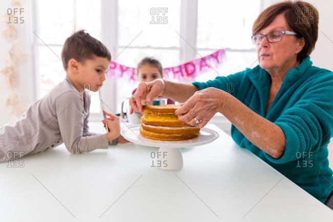 Kids and woman assembling layer cake