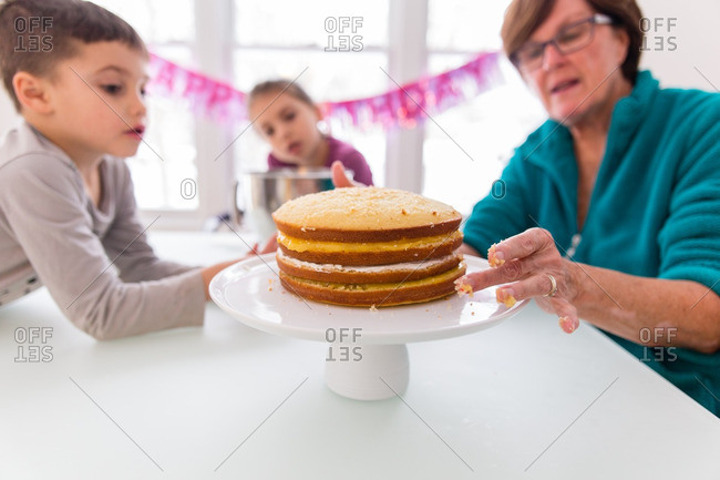 Kids and woman preparing layer cake