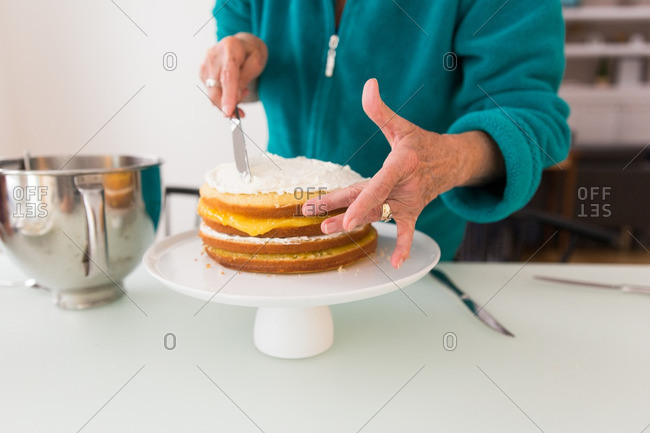 Woman frosting a layered cake