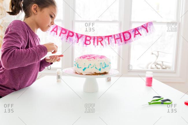 Girl putting sprinkles on birthday cake