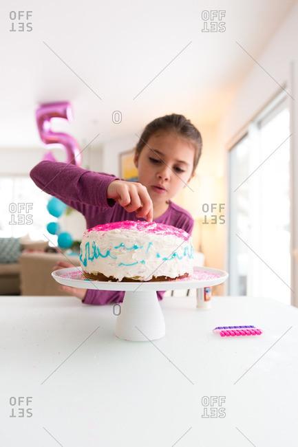 Girl putting sprinkles on a birthday cake