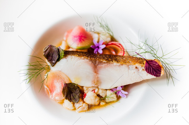 Fresh cooked fish dish with radishes and cauliflower