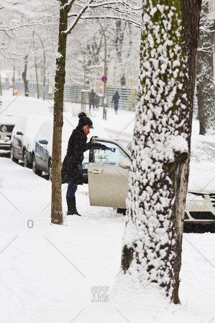 December 6, 2012 - Berlin, Germany: Woman cleans off her car windows after a heavy winter snowfall