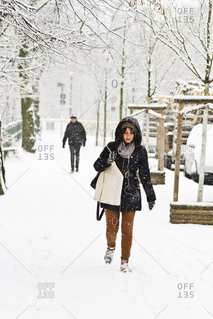 December 6, 2012 - Berlin, Germany: Young woman with shopping bag walking after a heavy snowfall