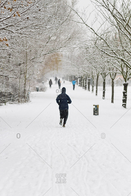 Person jogs in park after a heavy snowfall in Berlin