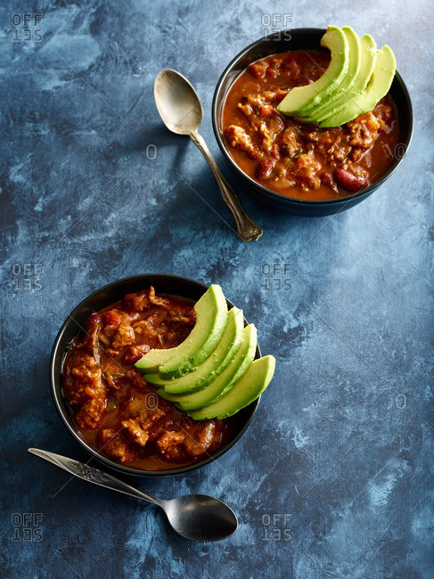 Bowls of chili with sliced avocado