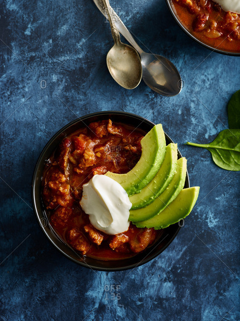 Bowls of chili with sliced avocado and sour cream