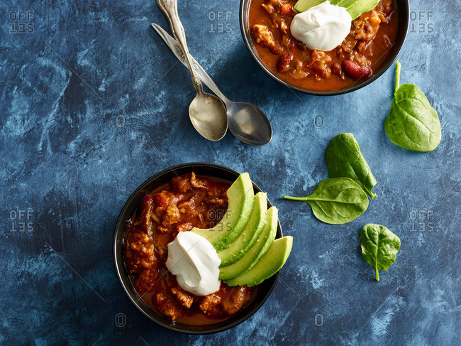 Bowls of chili served with avocado and sour cream