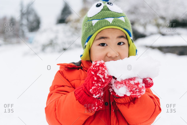 Young boy in monster hat tastes a chunk of snow