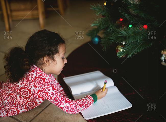 Girl by Christmas tree writing