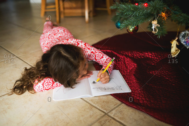 Girl by Christmas tree writing letter