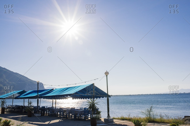 Waterfront dining tables set up under tents