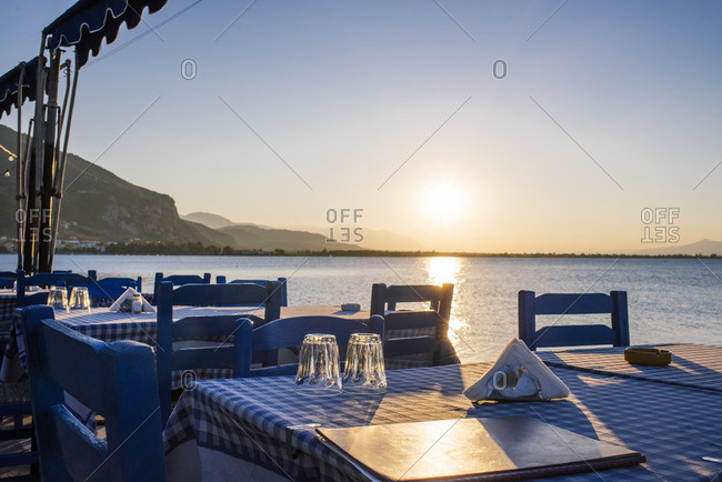 Waterfront dining tables at sunset