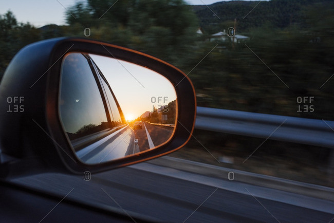 Vehicle rearview mirror reflecting sunset