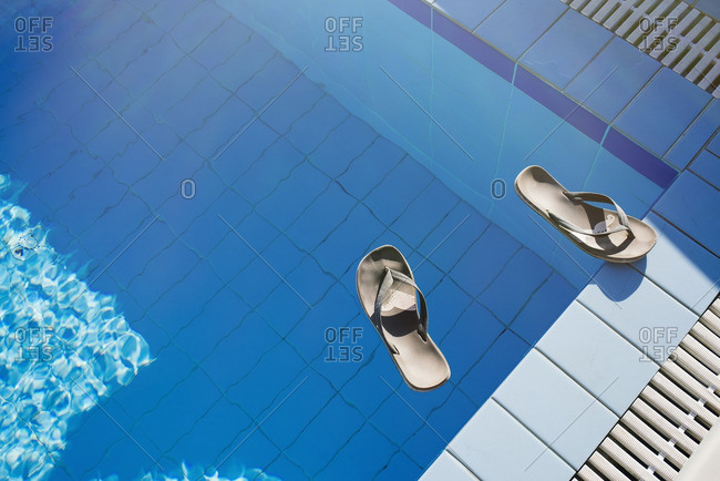 Flip flops float on the surface of a pool