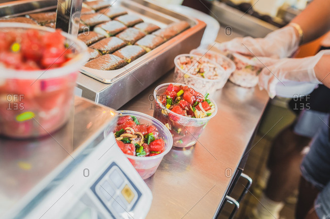 Close up of three poke orders being prepared