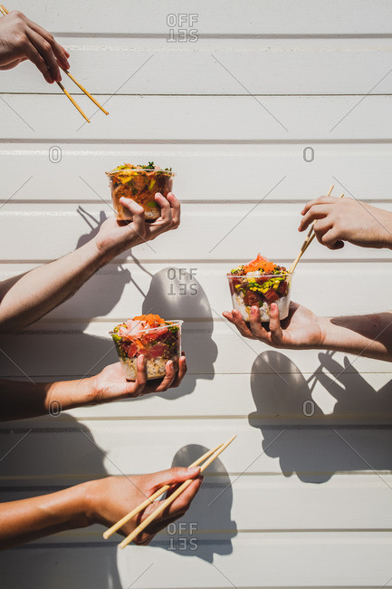 Many hands holding poke bowls and chopsticks in front of white background