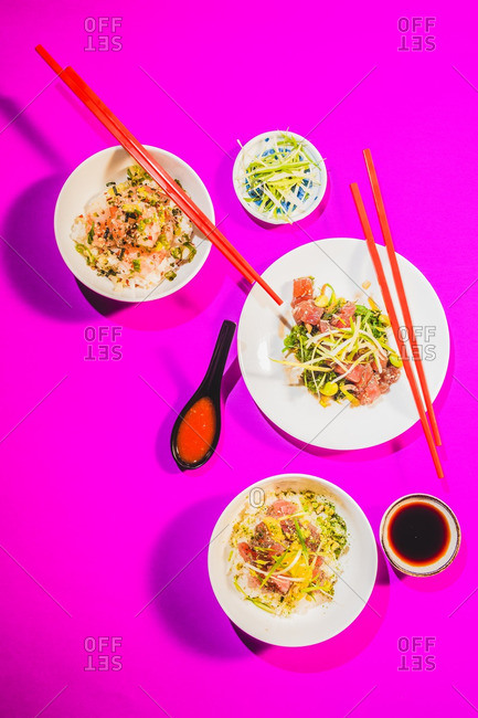 Lay flat of three poke dishes on bright magenta background