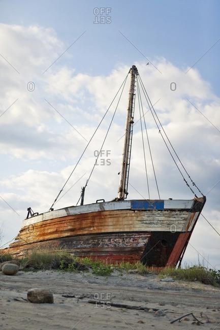 Rotting ship abandoned on sandy beach