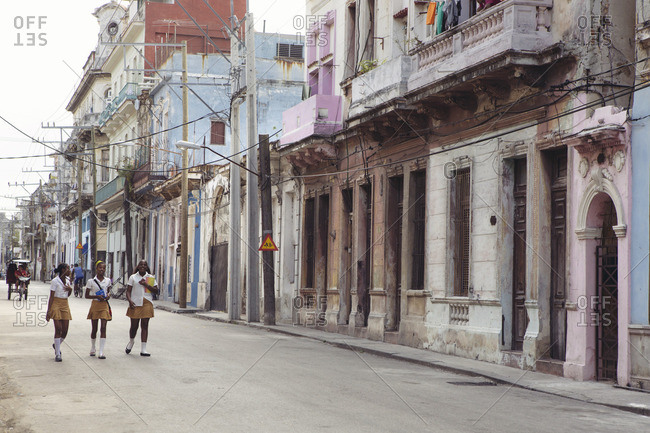 Havana, Cuba - March 10, 2015: Three girls in school uniforms walk down a street in Havana, Cuba