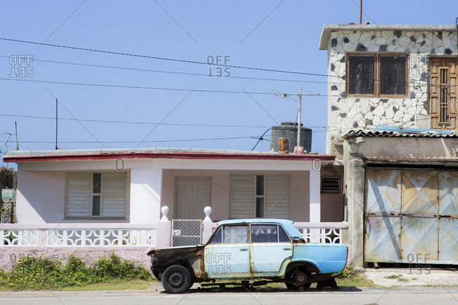 Havana, Cuba - March 13, 2015: A rusted out car in front of a house in suburban Havana, Cuba