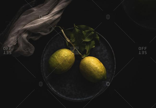 Fresh ripe citrus. Lemons, limes with white napkin on dark background