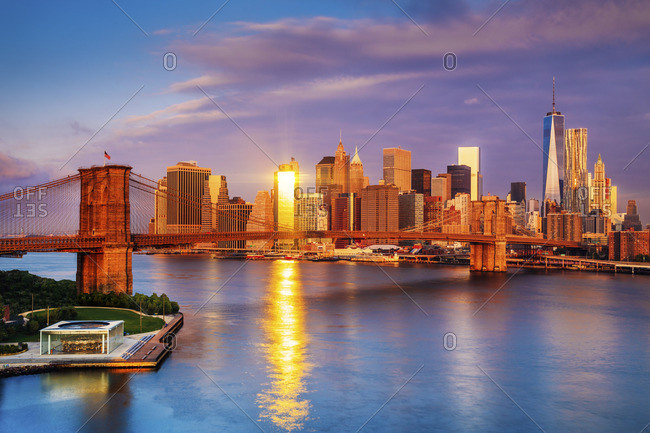 Brooklyn Bridge and Manhattan skyline with One World Trade Center and Freedom Tower at sunrise