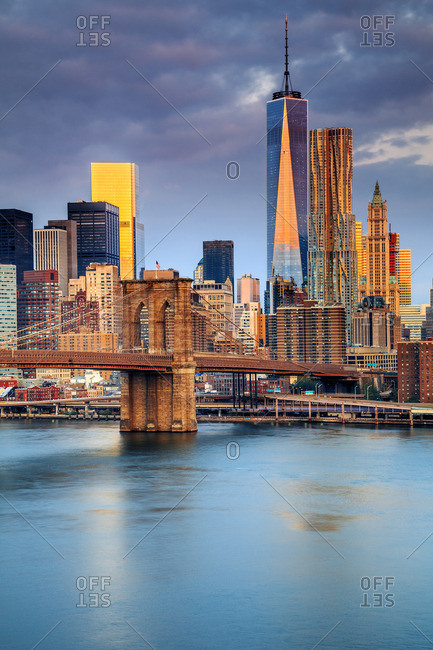 Lower Manhattan, Manhattan, New York City, United States, USA - December 22, 2016: Brooklyn Bridge and Manhattan skyline with One World Trade Center and Freedom Tower at sunrise