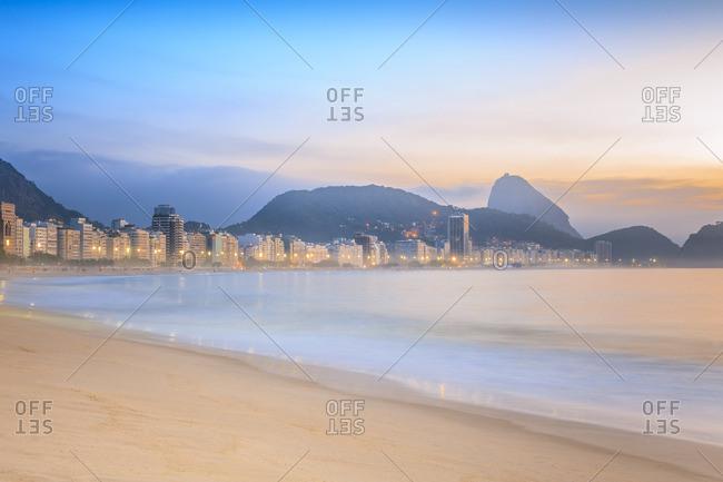 Copacabana, Rio de Janeiro, Rio de Janeiro, Brazil - December 22, 2016: The beach at sunrise and Sugarloaf Mountain (Pao de Acucar) in the background