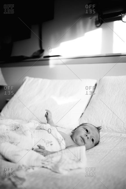 Baby boy lying awake on bed