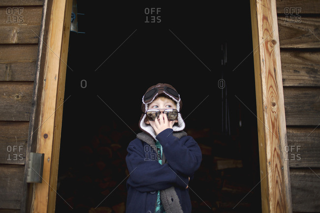Boy in aviator goggles in shed door