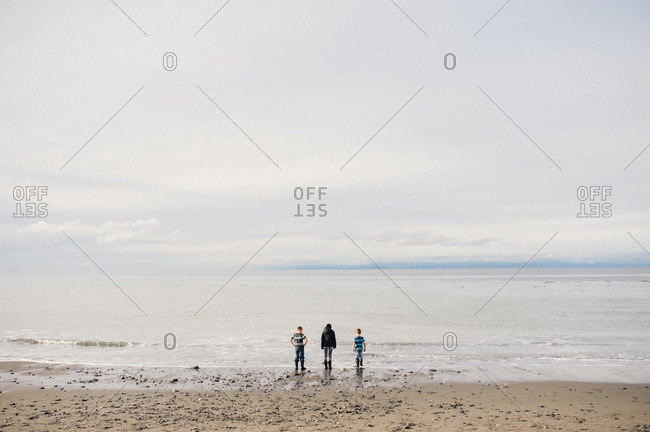 Three kids side by side on beach