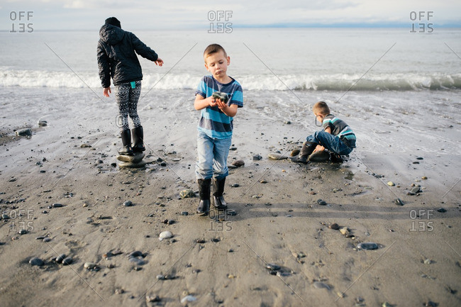 Three kids on beach in cool weather