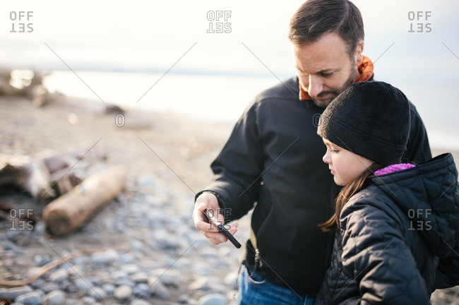 Man and girl with phone on winter beach