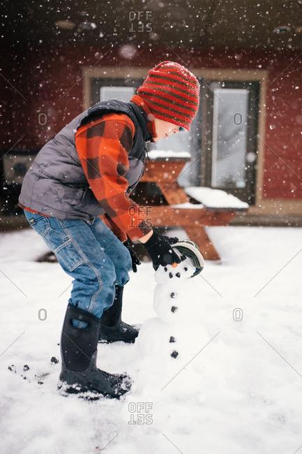 Boy building a snow man in yard