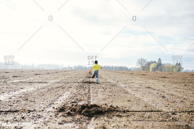 Boy running in muddy field