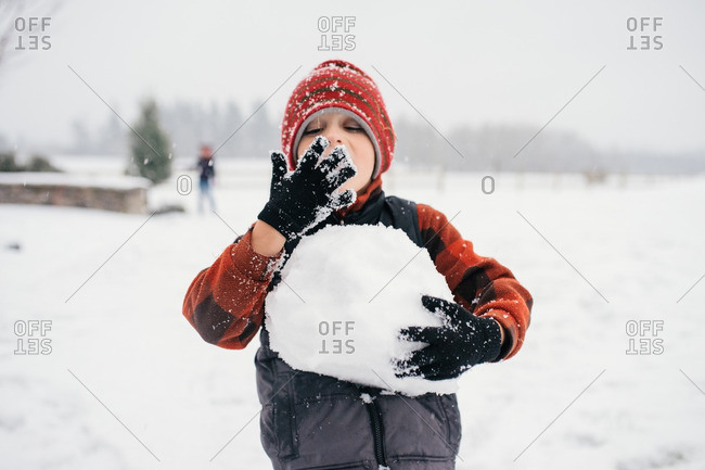 Boy eating snow holding snowball