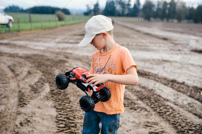 Boy holding toy car in farm field