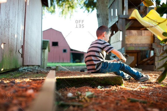 Boy sitting alone in farm yard